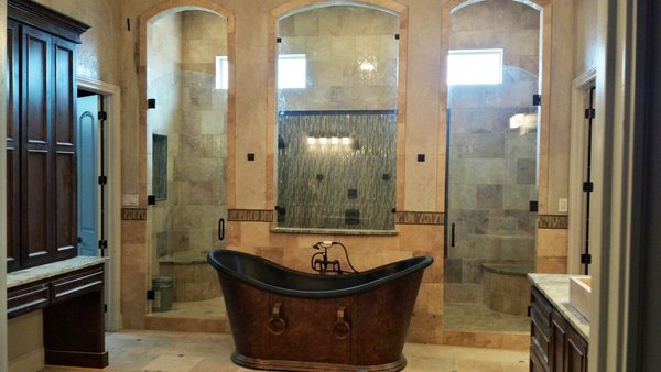Modern home with bath room, granite counter, freestanding tub, travertine floor, and enclosed shower. Arch top frameless doors and fixed panel  Photo 2 of Custom Frameless Shower Enclosure Projects