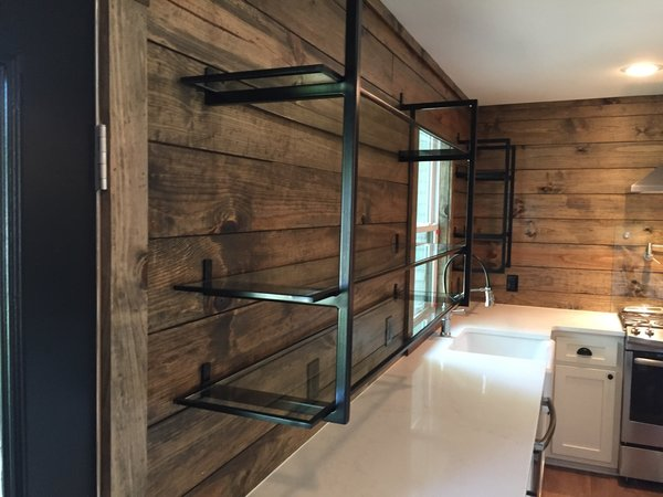 Modern home with kitchen, metal cabinet, wood backsplashe, and undermount sink. Powder Coated Black Steel Brackets & Rings with Glass Shelves by Anderson Glass Photo 2 of Shelving Units