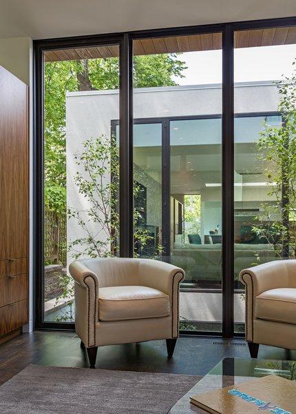 Modern home with trees, garden, picture window type, casement window type, metal, office, den, sun room, storage, chair, and dark hardwood floor. Photo 15 of Calhoun Pavilions Residence