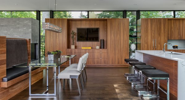 Modern home with chair, table, bench, storage, accent lighting, pendant lighting, stools, bar, dark hardwood floor, engineered quartz counter, dining room, drop in sink, and ceiling lighting. Photo 9 of Calhoun Pavilions Residence