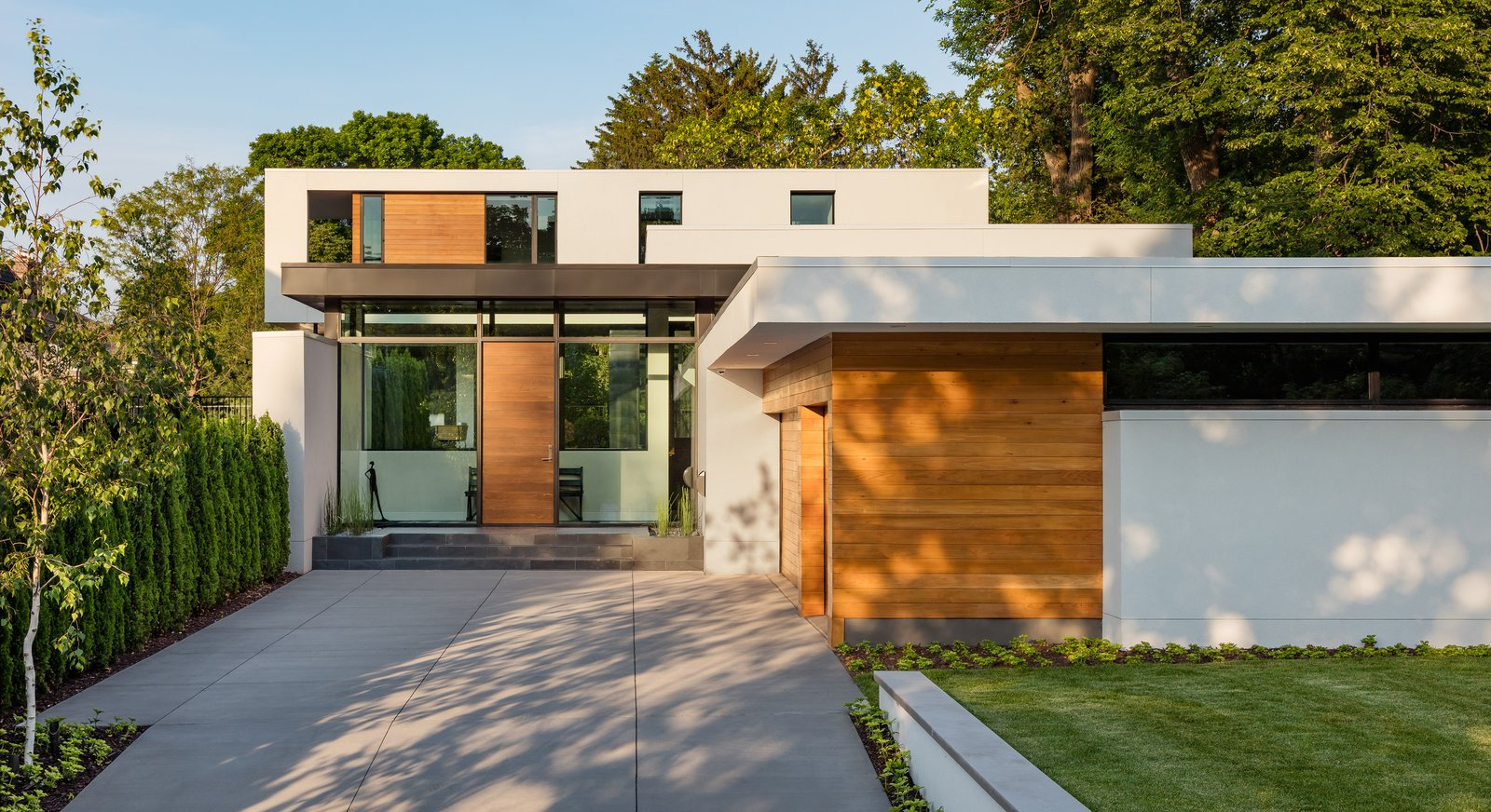 Tagged: Attached Garage, Front Yard, Wood, Swing Door Type, Exterior, Metal, Outdoor, Trees, Garden, and Raised Planters.  Calhoun Pavilions Residence by Peterssen/Keller Architecture