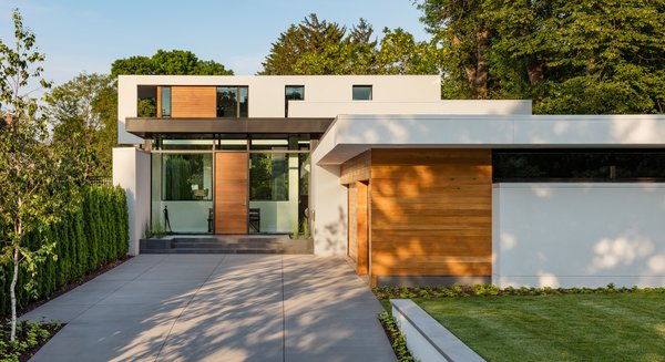 Modern home with attached garage, front yard, wood, swing door type, exterior, metal, outdoor, trees, garden, and raised planters. Photo  of Calhoun Pavilions Residence