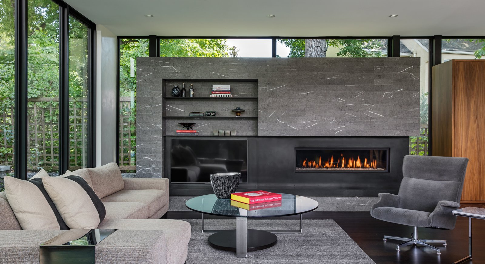 Tagged: Living Room, Ribbon Fireplace, Corner Fireplace, Coffee Tables, Gas Burning Fireplace, Sectional, Bookcase, Recliner, and Dark Hardwood Floor.  Calhoun Pavilions Residence by Peterssen/Keller Architecture