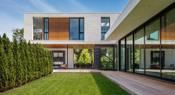 Modern home with trees, gardens, walkways, side yard, wood patio, porch, deck, exterior, metal, sliding door type, windows, picture window type, casement window type, and awning window type. Photo 5 of Calhoun Pavilions Residence