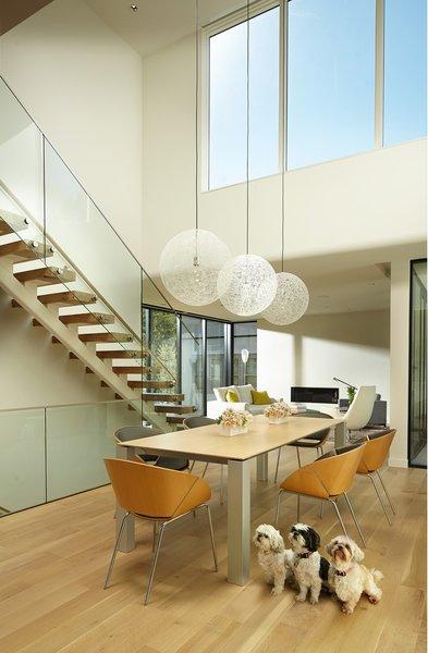 Modern home with wood tread, glass railing, dining room, chair, table, light hardwood floor, accent lighting, and pendant lighting. Photo 11 of Sheridan Residence
