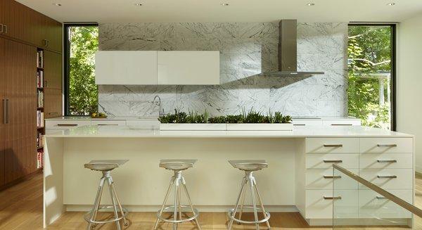 Modern home with kitchen, engineered quartz counter, wood cabinet, light hardwood floor, refrigerator, stone tile backsplashe, ceiling lighting, range hood, cooktops, and drop in sink. Photo 13 of Sheridan Residence