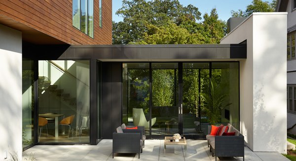Modern home with outdoor, pavers patio, porch, deck, wood patio, porch, deck, metal patio, porch, deck, concrete patio, porch, deck, back yard, garden, and trees. Photo 6 of Sheridan Residence