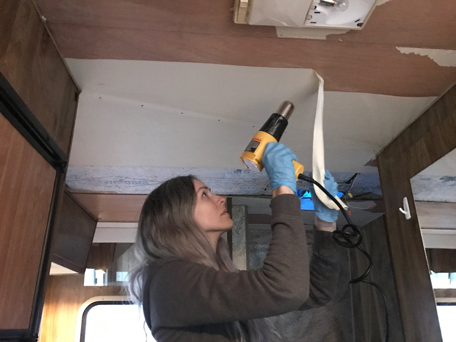 Kamarul removing wallpaper from the RV's ceiling. A Portland Couple Renovate a 1982 RV, Turning It Into Their New Home - Photo 5 of 13