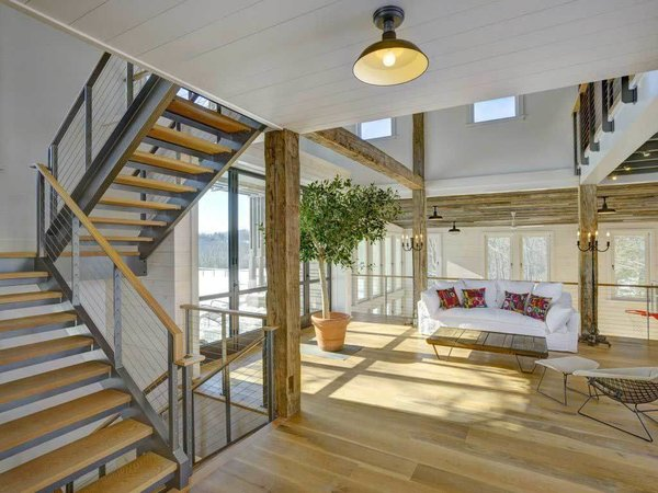 Modern home with living room, coffee tables, floor lighting, ceiling lighting, sofa, pendant lighting, and light hardwood floor. his great room has a comfortable living space that overlooks the indoor basket ball court. The multi-level double stringer switchback stair case has steel stringers with wood treads.  Photo  of Rustic Modern Party Barn