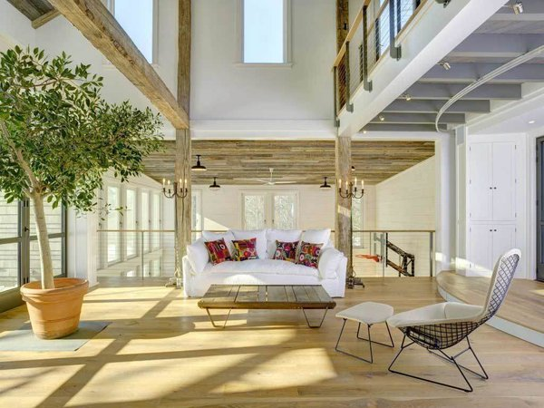 Modern home with living room, sofa, pendant lighting, coffee tables, ottomans, and light hardwood floor. This room quickly turns from great room to theater with an indoor stage. Photo 2 of Rustic Modern Party Barn