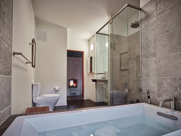 Modern home with bath room, soaking tub, porcelain tile floor, engineered quartz counter, undermount sink, whirlpool tub, alcove tub, enclosed shower, drop in tub, ceramic tile wall, corner shower, and two piece toilet. The two-sided Tulikivi stove is visible from the master bath. Photo 8 of Mill Pond House