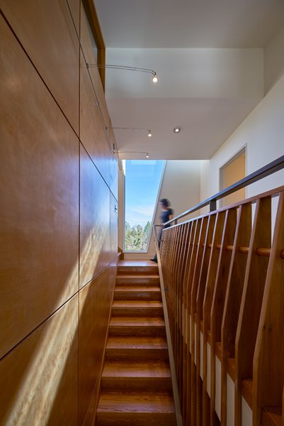 Modern home with staircase, wood tread, and wood railing. The balustrade is composed of wood fins.  Photo 11 of Mill Pond House