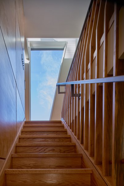Modern home with staircase, wood tread, and wood railing. Wood fin balustrade. Photo 12 of Mill Pond House