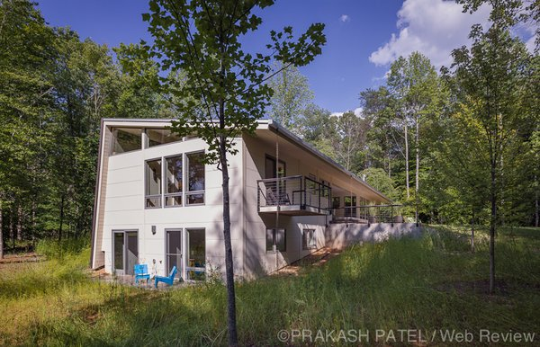Modern home with outdoor, slope, side yard, woodland, field, grass, trees, and concrete patio, porch, deck. Consistent to passive solar design, windows are larger and shaded by overhangs on the south facade. Photo 4 of Dogtrot at Stony Point