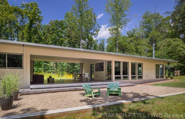 Modern home with outdoor, back yard, trees, grass, concrete patio, porch, deck, and small patio, porch, deck. All the public areas, including the living, dining area and kitchen are housed together in the eastern wing of the house. On the ground level of the western wing are the studio office and master bedroom.  On the lower level are three bedrooms that are partially embedded in the sloping hillside. Photo 6 of Dogtrot at Stony Point