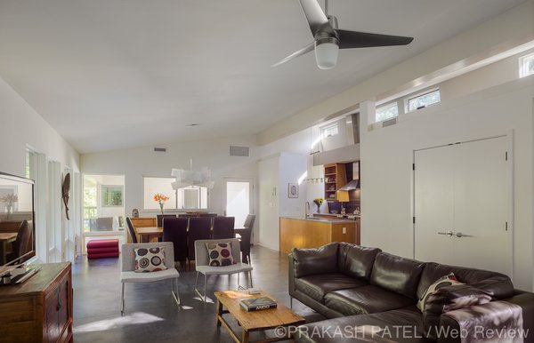 Modern home with living room, chair, sofa, sectional, ceiling lighting, and concrete floor. The living room looks onto the dogtrot. Photo 11 of Dogtrot at Stony Point
