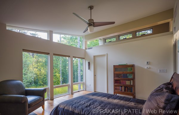 Modern home with bedroom, bed, bookcase, chair, ceiling lighting, and medium hardwood floor. The master bedroom enjoys south facing windows. Photo 13 of Dogtrot at Stony Point