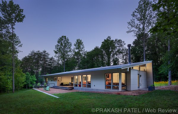 Modern home with outdoor, back yard, grass, trees, small patio, porch, deck, and concrete patio, porch, deck. Evening view.  The owner co-habitate with turkey, fox and other wildlife which they enjoy from the dogtrot terrace. Photo 14 of Dogtrot at Stony Point