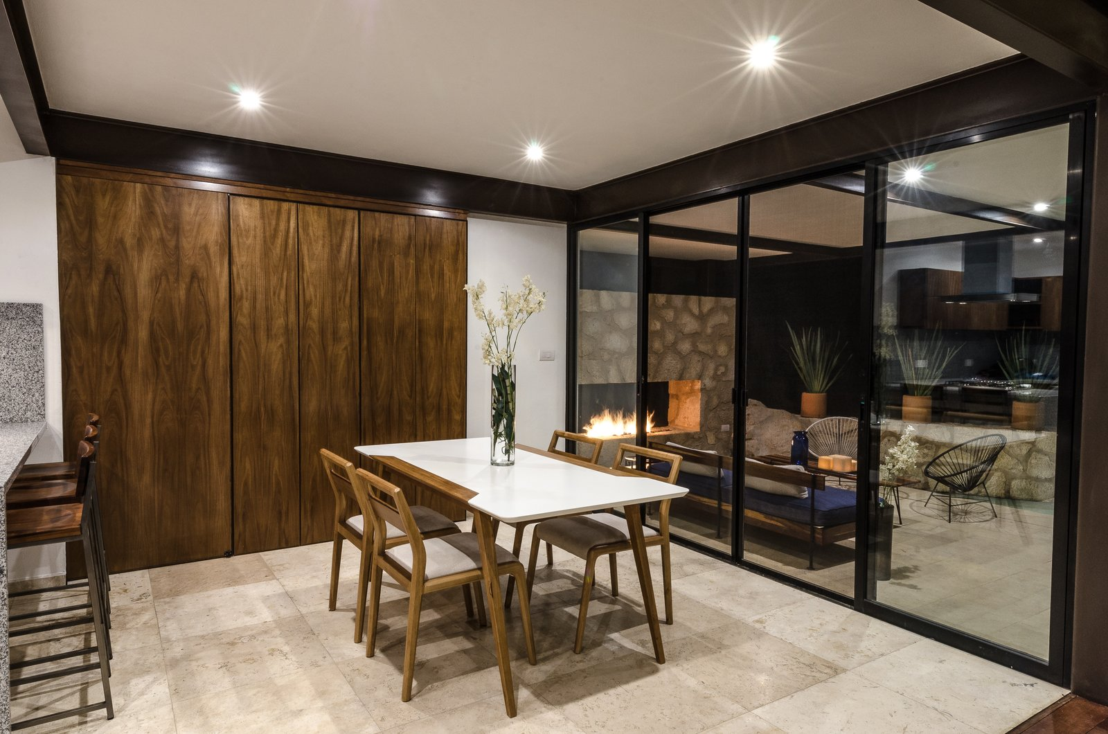 Dinning and terrace Tagged: Dining Room, Two-Sided Fireplace, Table, Travertine Floor, Chair, Storage, and Ceiling Lighting.  CQ12 by tescala