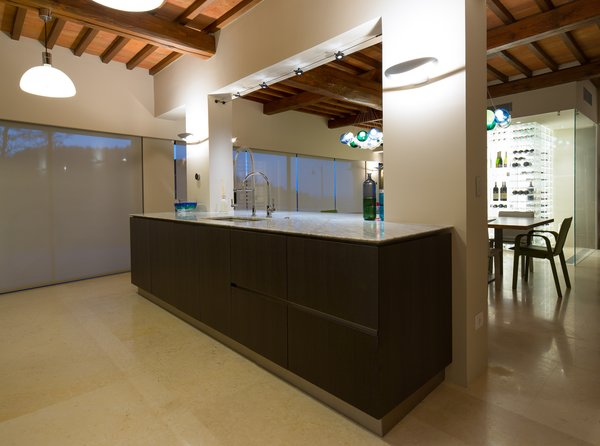 Modern home with marble counter, wood cabinet, wine cooler, drop in sink, pendant lighting, kitchen, track lighting, and wall lighting. Photo 6 of Campo al Doccio