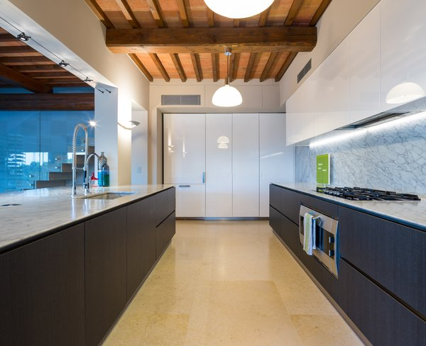 Modern home with marble counter, stone slab backsplashe, track lighting, pendant lighting, wall lighting, refrigerator, drop in sink, white cabinet, wood cabinet, staircase, glass railing, and stone tread. Photo 8 of Campo al Doccio