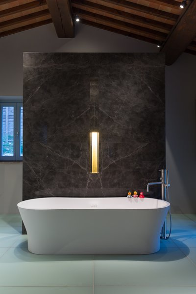 Modern home with bath room, freestanding tub, stone slab wall, and accent lighting. Photo 12 of Campo al Doccio