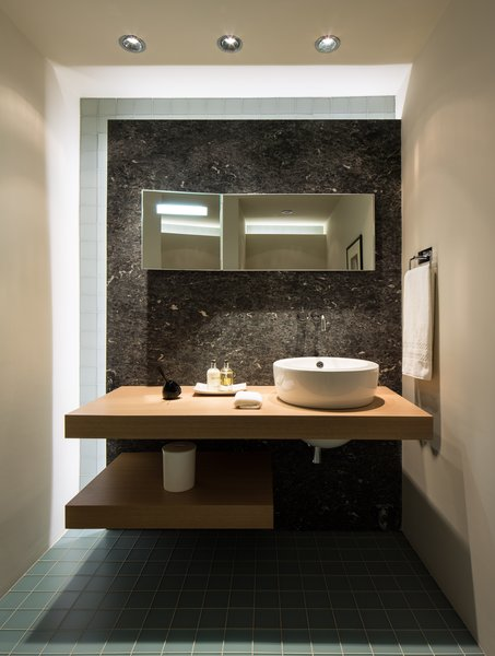 Modern home with bath room, stone slab wall, vessel sink, wood counter, and ceiling lighting. Photo 13 of Campo al Doccio