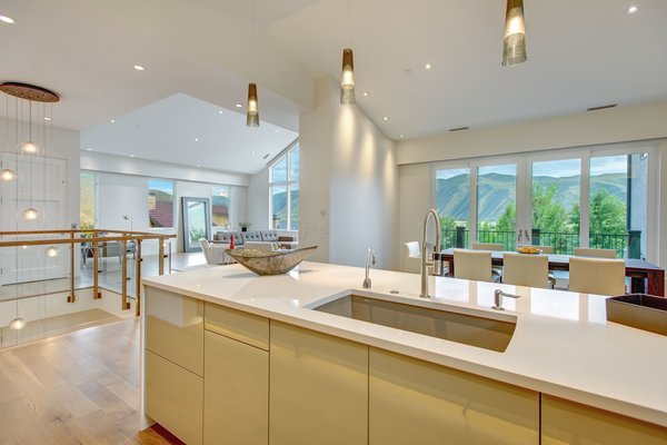 Modern home with white cabinet, medium hardwood floor, drop in sink, pendant lighting, dining room, and ceiling lighting. Photo 3 of The Wilds