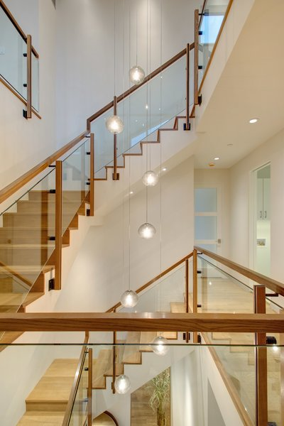 Modern home with glass railing, living room, wood tread, wood railing, and pendant lighting. Photo 8 of The Wilds