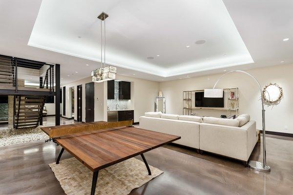 Modern home with family room, metal railing, wood tread, living room, sofa, recessed lighting, accent lighting, and pendant lighting. Photo 14 of Saddleback Lane