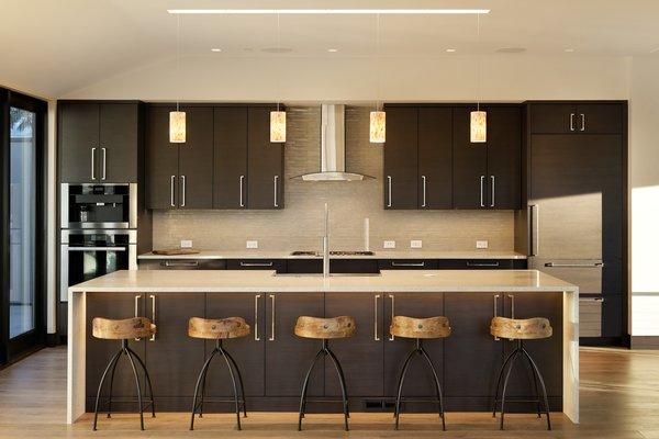 Modern home with kitchen, wood cabinet, pendant lighting, and medium hardwood floor. Photo 11 of Saddleback Lane