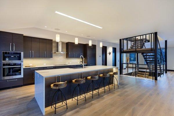 Modern home with wood cabinet, pendant lighting, medium hardwood floor, recessed lighting, staircase, drop in sink, accent lighting, wood tread, and metal railing. Photo 10 of Saddleback Lane