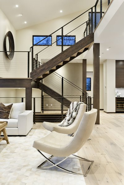 Modern home with chair, medium hardwood floor, recessed lighting, staircase, wood tread, and metal railing. Photo 5 of Mustang Circle