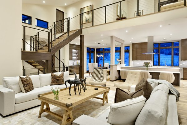 Modern home with coffee tables, sofa, chair, ceiling lighting, medium hardwood floor, staircase, metal railing, and wood tread. Photo 4 of Mustang Circle