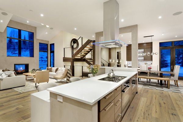 Modern home with medium hardwood floor, range hood, wood counter, range, two-sided fireplace, dining room, recessed lighting, bench, chair, pendant lighting, and table. Photo 8 of Mustang Circle