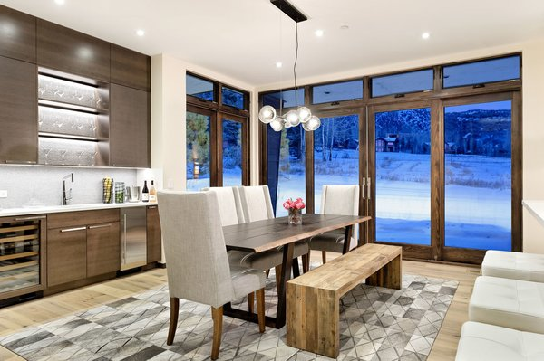 Modern home with bench, chair, pendant lighting, medium hardwood floor, table, recessed lighting, kitchen, wine cooler, and beverage center. Photo 9 of Mustang Circle