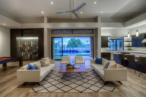 Modern home with living room, chair, sofa, recessed lighting, medium hardwood floor, coffee tables, and pendant lighting. Fanfol Family Room with 546 Bottle Custom Wine Wall Photo 3 of Fanfol House