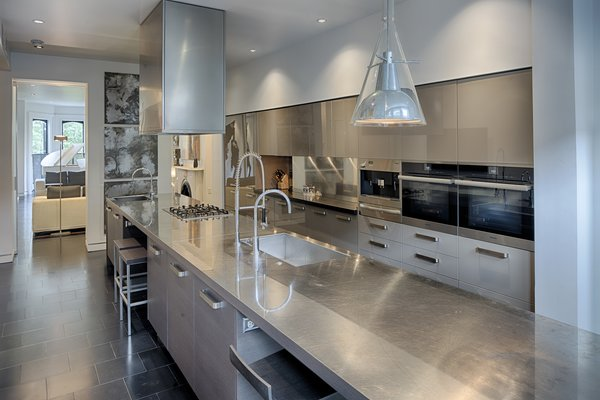 Modern home with kitchen, metal counter, refrigerator, and wall oven. Photo 3 of 112 West Gaston Street