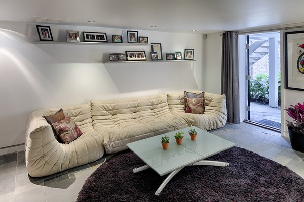 Modern home with living room, sofa, recessed lighting, coffee tables, and slate floor. Photo 7 of 112 West Gaston Street