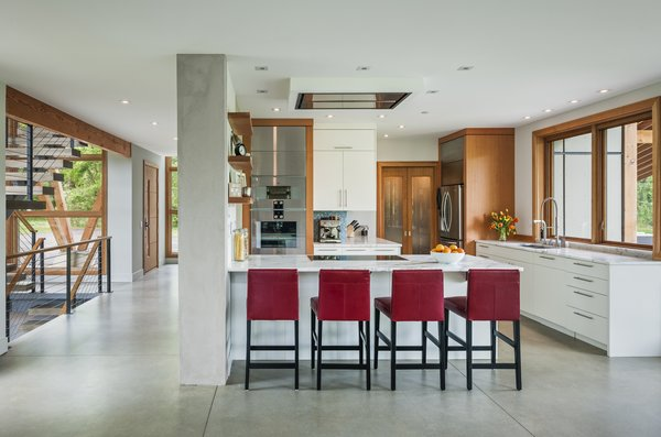 Modern home with kitchen, marble counter, wood cabinet, white cabinet, refrigerator, concrete floor, recessed lighting, cooktops, wall oven, and undermount sink. Photo 5 of Leaning Timber House