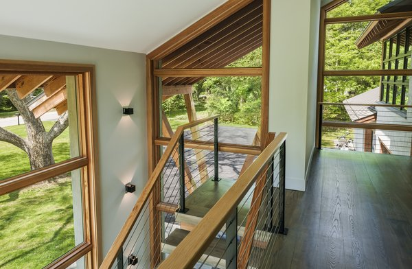 Modern home with dark hardwood floor, staircase, metal railing, and wood tread. Photo 8 of Leaning Timber House
