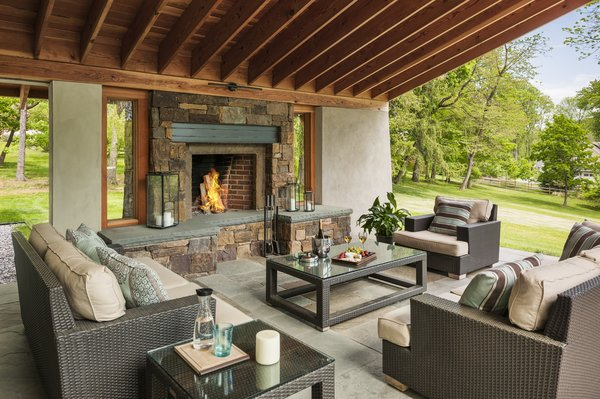 Modern home with outdoor, back yard, trees, stone patio, porch, deck, and grass. Photo 7 of Leaning Timber House