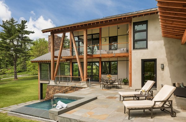 Modern home with outdoor, trees, grass, back yard, small pool, stone patio, porch, deck, hanging lighting, and large patio, porch, deck. Photo 9 of Leaning Timber House