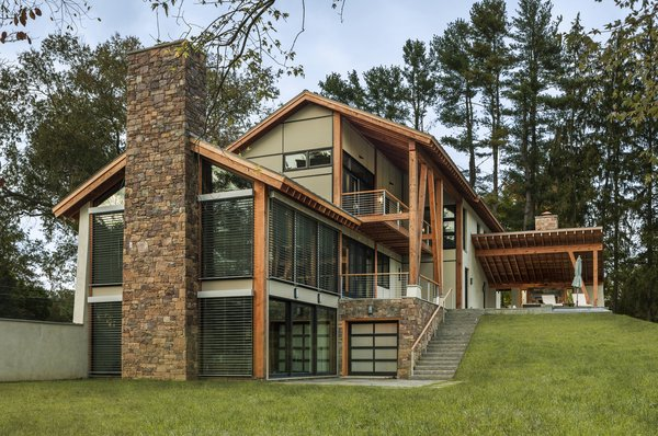 Modern home with outdoor, back yard, side yard, hardscapes, grass, hanging lighting, large patio, porch, deck, and stone patio, porch, deck. Photo  of Leaning Timber House