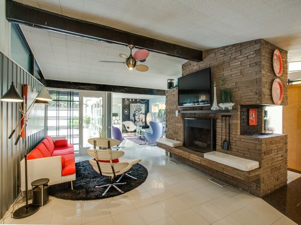 Modern home with living room, bench, chair, sofa, porcelain tile floor, end tables, ceiling lighting, and standard layout fireplace. Photo 5 of Candy-Colored Mid-Century Modern Throwback