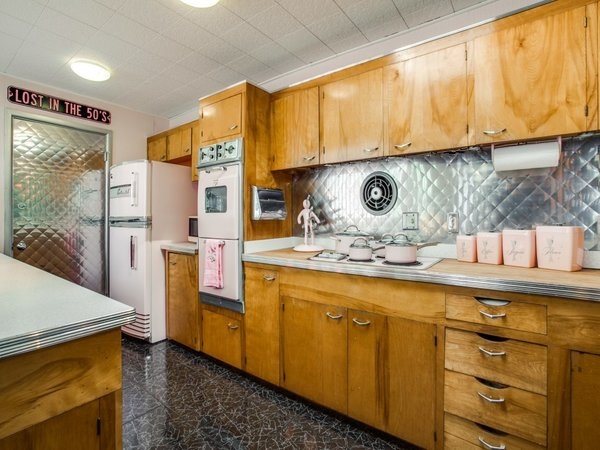 Modern home with kitchen, metal backsplashe, wood cabinet, ceiling lighting, wood counter, and cooktops. Photo 13 of Candy-Colored Mid-Century Modern Throwback