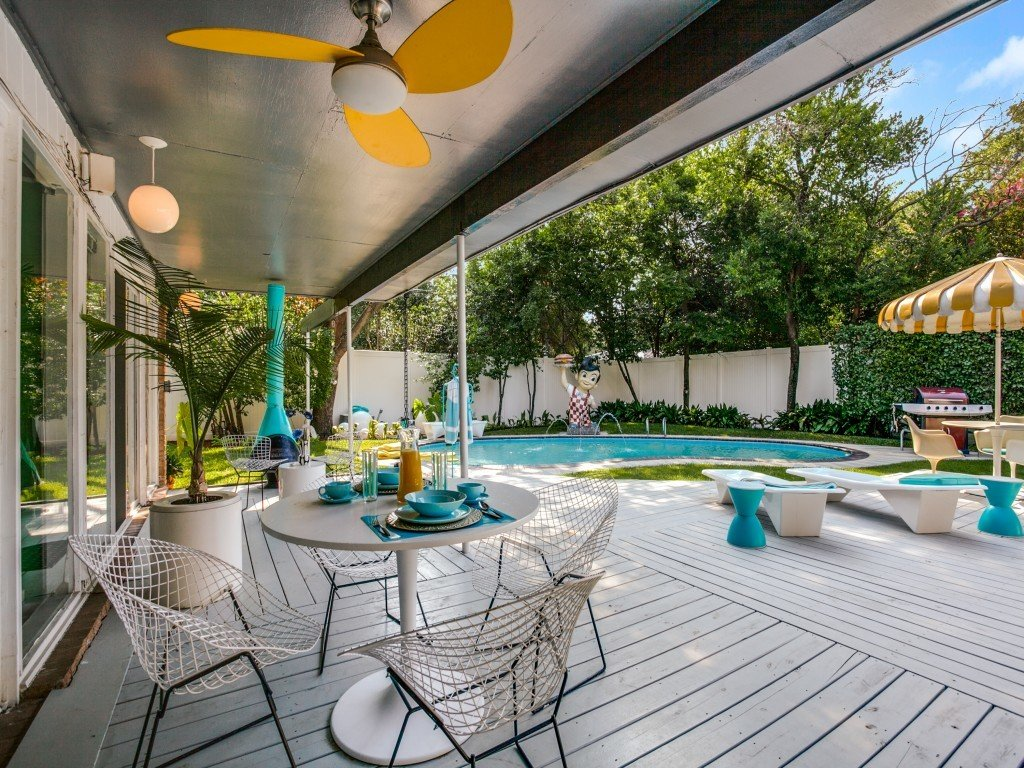 Tagged: Outdoor, Back Yard, Trees, Grass, Swimming Pools, Tubs, Shower, Large Patio, Porch, Deck, Large Pools, Tubs, Shower, Wood Patio, Porch, Deck, Vertical Fences, Wall, and Wood Fences, Wall.  Candy-Colored Mid-Century Modern Throwback by Zillow