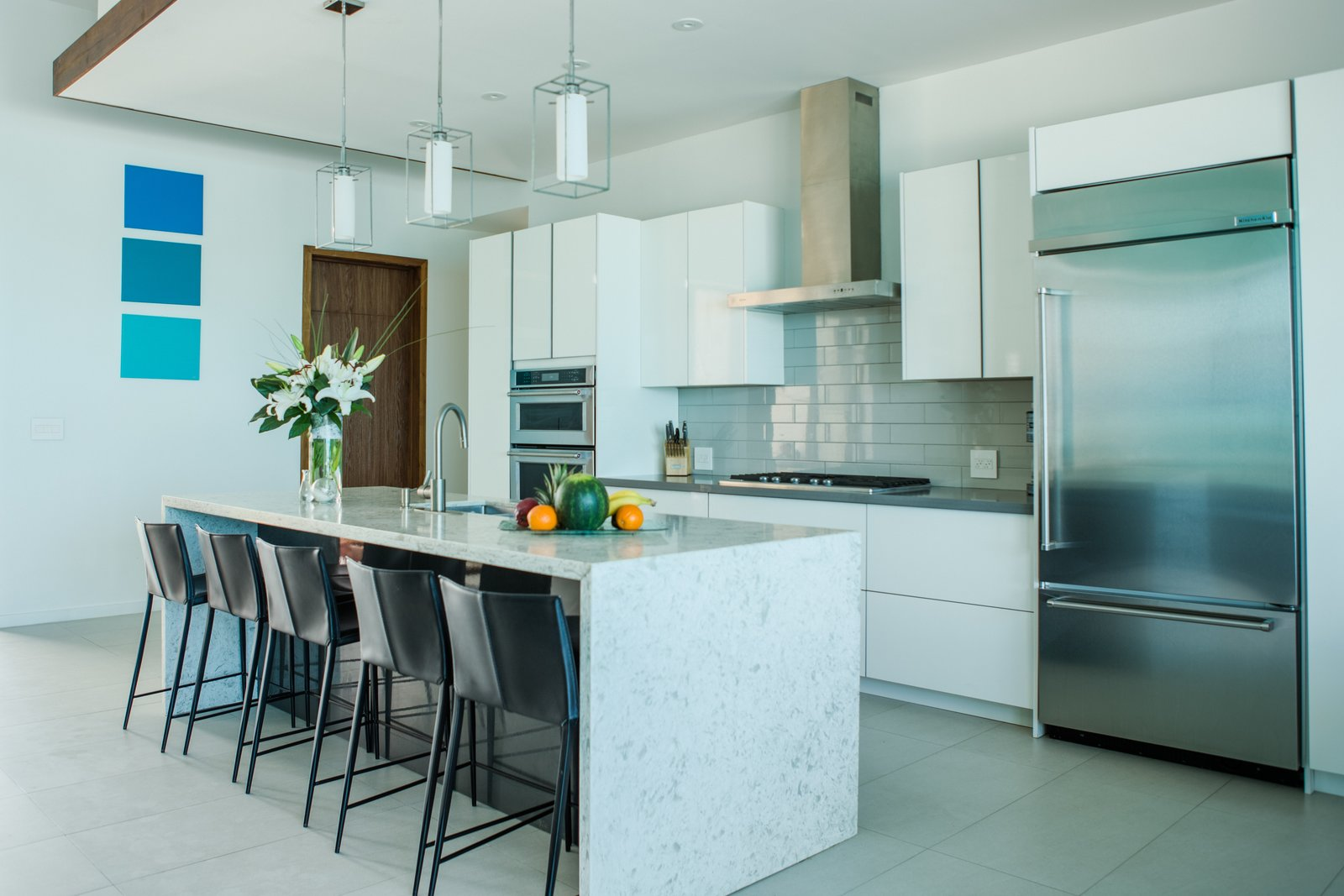 Tagged: Kitchen, White Cabinet, Subway Tile Backsplashe, Porcelain Tile Floor, Pendant Lighting, Refrigerator, Cooktops, Marble Counter, and Drop In Sink.  Tip of the Tail Villa by Zillow