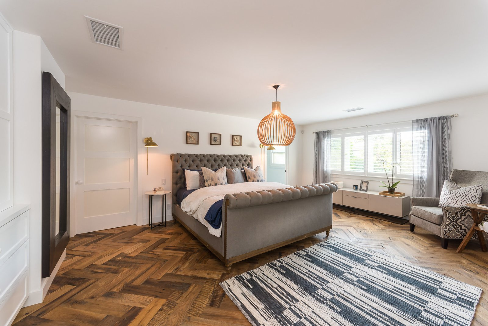Tagged: Bedroom, Chair, Bed, and Medium Hardwood Floor.  Mid-Century Meets Boho Chic by Zillow