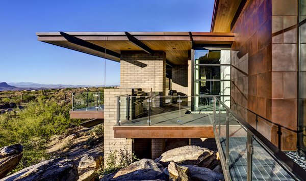 Modern home with outdoor, rooftop, desert, front yard, side yard, boulders, small pool, small patio, porch, deck, wire fence, metal fence, and metal patio, porch, deck. Photo  of Canyon Pass Home at Dove Mountain